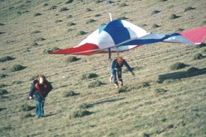 Photo of a man carrying a fully rigged hang glider up a hill