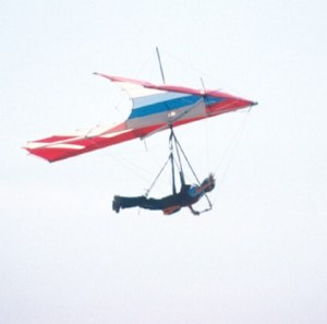 Photo of a 1970s hang glider in flight