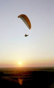 Paraglider flying at sunset