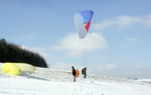 Photo of two paragliders preparing to launch from snowy ground