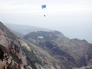 Photo of a paraglider in flight over rugged terrain