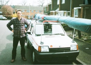 Photo of a man standing beside a car with a hang glider on its roof