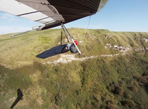 Everard Cunion flying a hang glider at Ringstead, Dorset, England