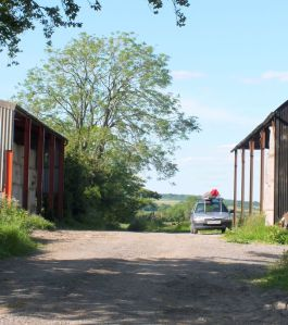 Farm buildings and car with hang glider on roof