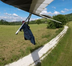 Hang glider crossing a farm track on landing final