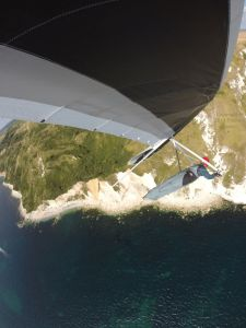Hang glider soaring coastal cliff