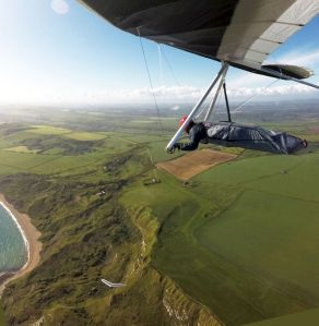 Hang glider soaring coastal cliffs