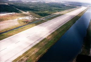 A flex-wing powered ultralight (middle left) shoots the space shuttle runway in Florida in about 1999