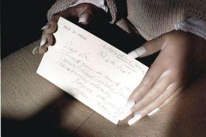A Realdoll holding a postcard written by Sigmund Freud