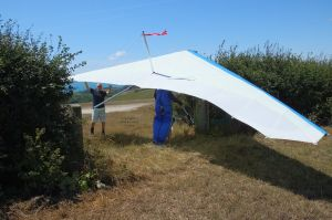 Getting a hang glider through the gate of the top landing field at Ringstead