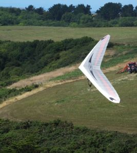Icaro Laminar hang glider in flight with a farm vehicle in the distance