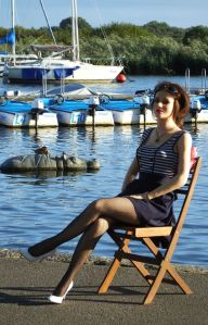 Life-size doll posing on quay-side with artificial hippo in water