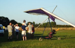 People next to a flexwing powered ultralight at sunset