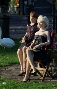 Mother and daughter life-size dolls sitting outdoors in a public place