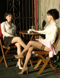 Two life-size dolls drinking coffee outdoors at sunset