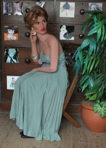 Life-size doll in long dress sitting with head turned and fingering earring