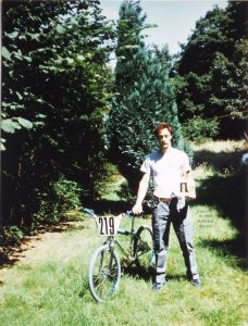 Rider posing in a garden with my BMX race bike and a trophy in August 1986