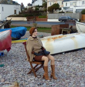 Faina Anatomical Doll sitting among boats on a beach
