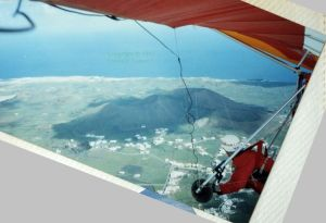View from an airborne hang glider of a coastal volcano in Lanzarote