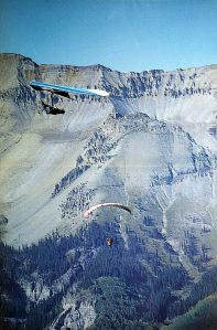 Art based on a photo by Leroy Grannis of a hang glider camera ship and a paraglider at Telluride, Colorado