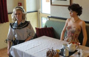 Two life size dolls at breakfast in a hotel