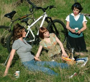 Life size dolls at a picnic with bicycles