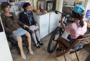 Three life size dolls with a bicycle in a kitchen