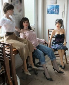 Three life size dolls in a kitchen