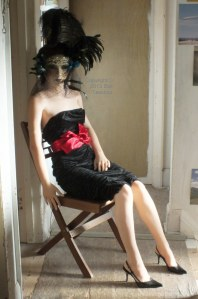 Life size doll wearing ball mask.