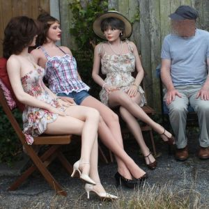 Three life size dolls sitting with their owner outdoors