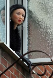Life size doll leaning out of an upstairs window