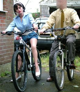 Life-size doll and owner on bicycles