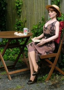 June life-size doll sitting outside