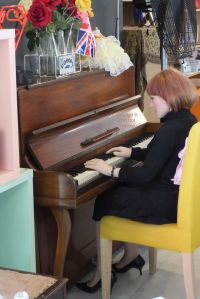 June life-size doll playing a piano in a cafe in Bournemouth