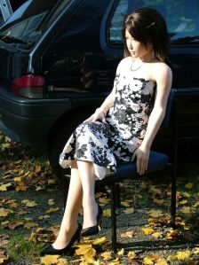 Laura 4woods sitting outdoors among autumn leaves