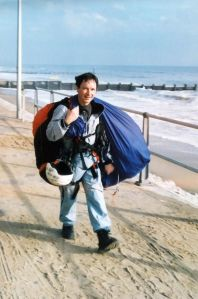 Luigi carries his paraglider and gear back at Bournemouth beach