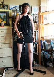 Raisa Anatomical Doll in a black dress and carrying an AK-47