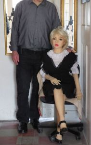 Sara YL doll sitting on a chair with her owner standing beside her