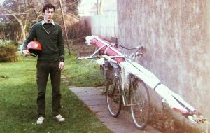 Everard Cunion with hang glider on bike in garden in 1975