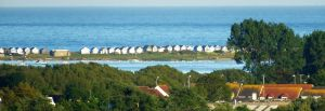 Beach huts on the sand bar off Hengistbury Head shimmering in the haze viewed from St. Catherine's Hill, Christchurch, Dorset, England, in May 2020