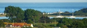 Beach huts and boats off Hengistbury Head viewed from St. Catherine's Hill, Christchurch, Dorset, England, in May 2020